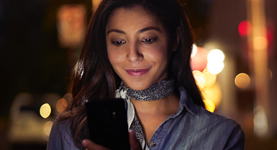 Smiling woman looking at phone