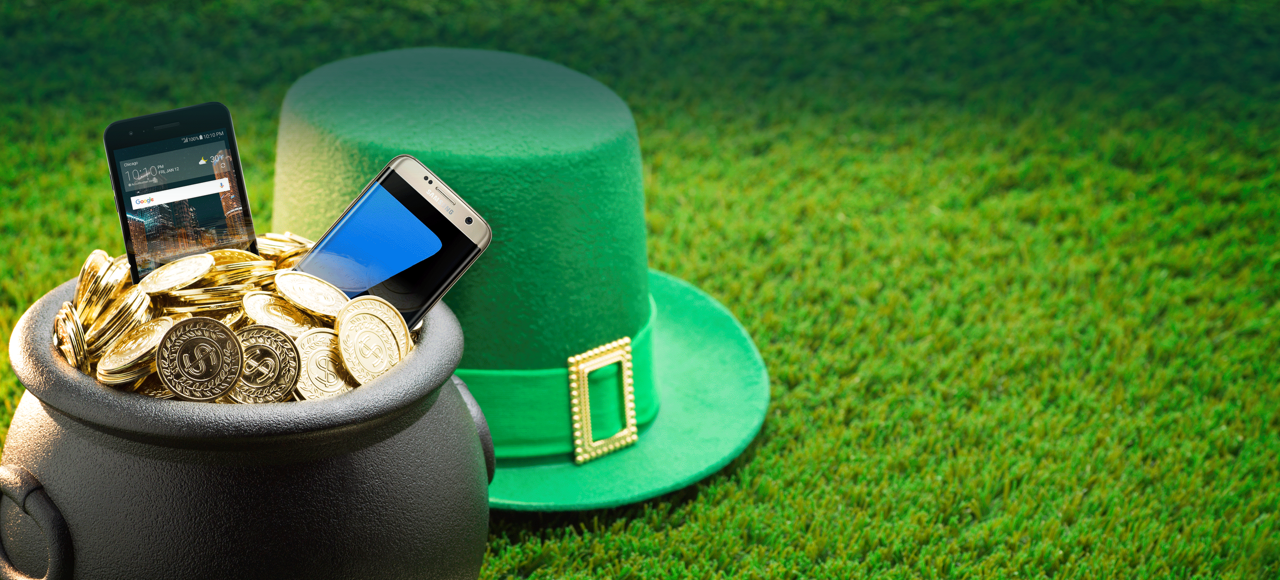 St. Patrick's hat next to a pot holding phones and gold
