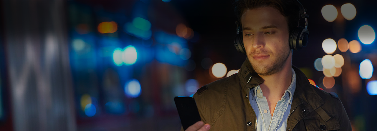 Man with headphones streaming music through his smartphone